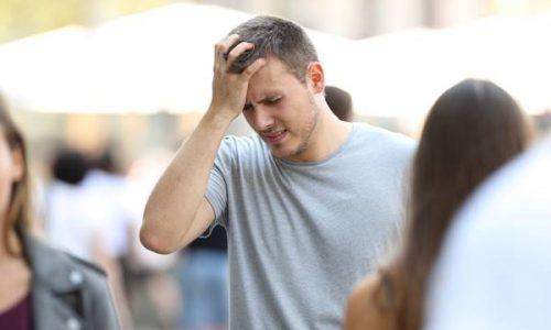 Portrait of a man suffering head ache walking on the street